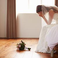 bridal anxiety - a bride sits on a bed with her head in her hands