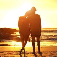 Couple stood watching sunset